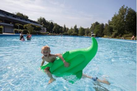 Junge plantscht im Schwimmbad