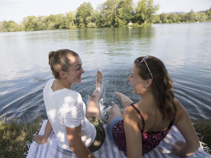 Zwei Frauen lassen die Füße im Rhein baumeln